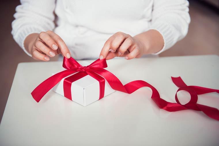 Aus gewebtem Kunststoff oder Stoff bestehende breite Geschenkbänder sind für eine normale Schleife auf einem Geschenk besonders gut geeigne