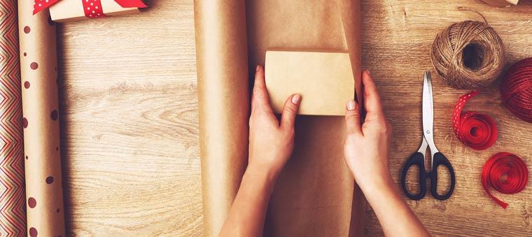 Bevor Sie das Geschenk in Geschenkpapier einschlagen, sollten Sie das Präsent auf der Innenseite des zugeschnittenen Papiers zentral aufstellen