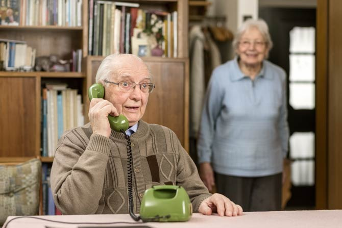 Älterer Herr am Festnetztelefon